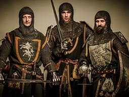 Three men dressed as knights in armour