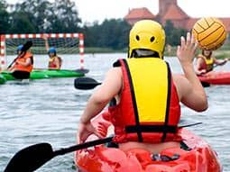 The back of a man kayaking, with others in the background