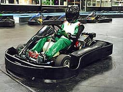 Someone sat in a go kart, on an indoor track, in green and white overalls