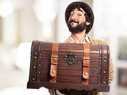 A man carrying a wooden chest