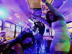 Women dancing inside a party bus under blue and purple lights