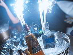 Sparklers and two bottles of spirits in an ice bucket, with glasses in the background