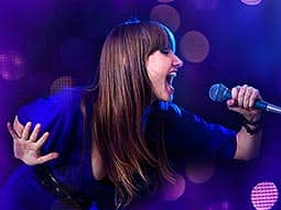 A woman singing into a mic, to a blue backdrop