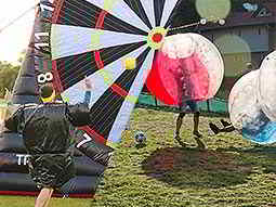 Split image of the back of a man running to a footdart board, and people playing in inflatable balls on a field