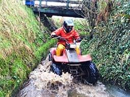 A man driving a quad bike through a river