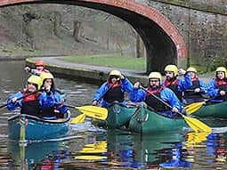 People in kayaks on the river travelling under a bridge