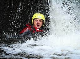 A man wearing a yellow helmet in a waterfall