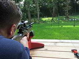 Close up of the back of a mans head and shoulder as he aims with an air rifle, set on a red stand outdoors