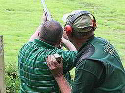 The back of a man aiming with a shotgun to the sky, as an instructor looks on and holds his arm