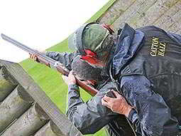 The back of a man aiming with a shotgum with an instructor looking on behind him