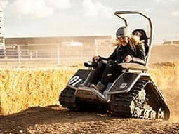 A woman driving an elektro kart on a field