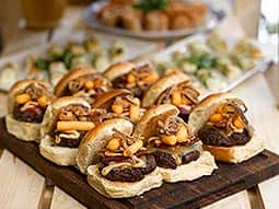 A platter of burger sliders, with other buffet-style food in the background