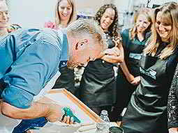 A man piping icing with women looking on