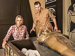 A man and woman with shocked faces, looking at a body in a sarcophagus