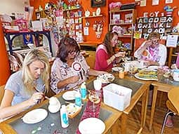 Women sitting around a table, painting their pottery in the studio