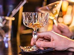 A mans hand holding a crystal glass stem, with rum in