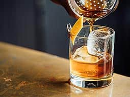 Whiskey being poured through a sieve and into a tumbler, over ice