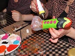 Two women decorating dildos