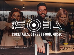 Image of a bartender behind a bar, stood making cocktails with two women, with the Bar Soba logo over the top