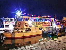 A white boat moored at a river bank at night