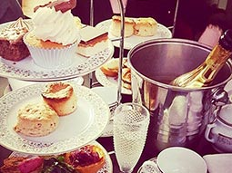 An image of afternoon tea and bottle of champagne in an ice bucket