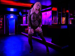 A man dressed as a woman in a blonde wig and sunglasses