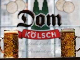 Two steins with Dom Kolsch in the background
