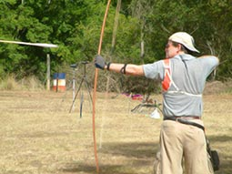 A man aiming with a bow and arrow during an outdoor archery session