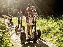 A group of people riding segways through a forest