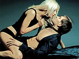 A woman straddling a man and pulling on his tie