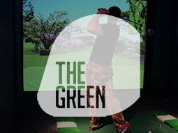 A man hitting a golf ball in a golf simulator with The Green logo overlapping him
