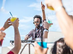 A DJ performing to a crowd of people outdoors