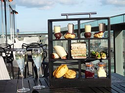 An afternoon tea on a black tiered stand, with two glasses of bubbly next to it