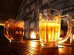 Two steins of beer, one illuminated by the backlight