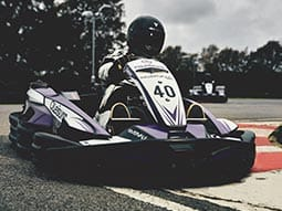 A person driving a go kart around a track, going over the edge of the track onto the grass