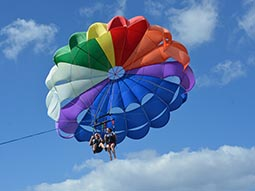 A multicoloured parachute with two people in the sky