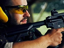 A man wearing a visor and holding a black assault rifle