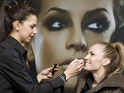 A woman receiving a makeover with an image of a heavily made up girl in the background