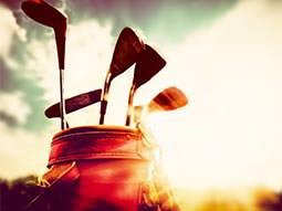 Close up of golf clubs in a bag to a sunset backdrop