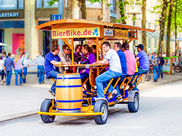 A group of people sitting on a beer bike on a street