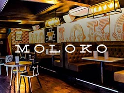 Some booths in Moloko with the bar