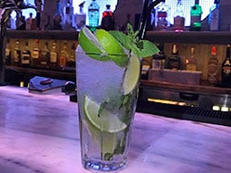 A mojito on the bar with lots of ice and limes in it