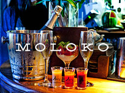Three shots, some drinks glasses and a bottle of Champagne chilling in a bucket, with Moloko's logo over it