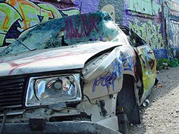 A car with graffiti on it, after being smashed up