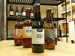 Bottles of craft beer on a table, with more bottles on a shelf, in the background
