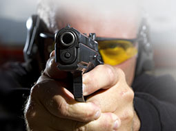 A man with safety glasses holding a gun in a shooting position