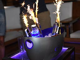 An ice bucket with bottles of alcohol and sparklers coming out
