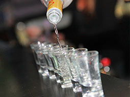 A row of shot glasses being filled with clear liquid