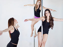 Women holding various positions on poles