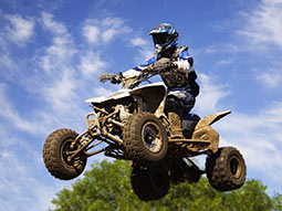 A person in mid air on a quad bike